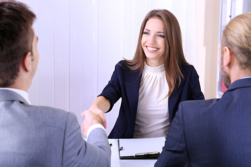 Female Job applicant shaking hands with interviewer